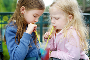 Two girls drinking slushie drink